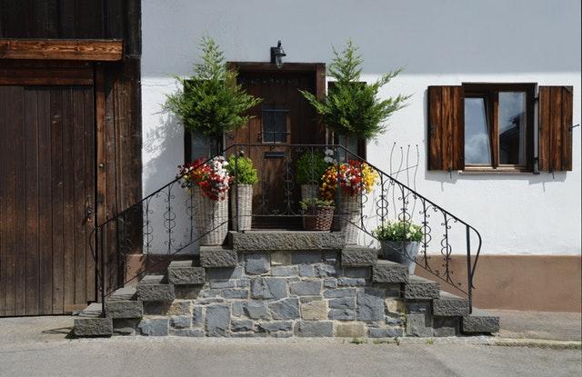 Biely rodinný dom s malými schodmi a zábradlím pred vchodovými dverami.jpg