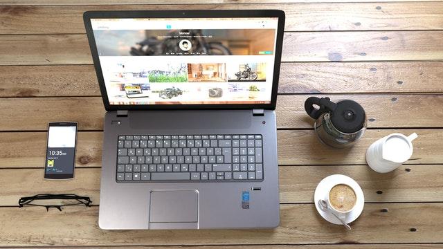 Notebook, mobil a káva položené na drevenom stole.jpg