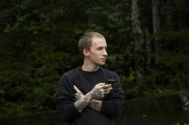 Muž s tetovaním na rukách stojí na terase pred lesom.jpg