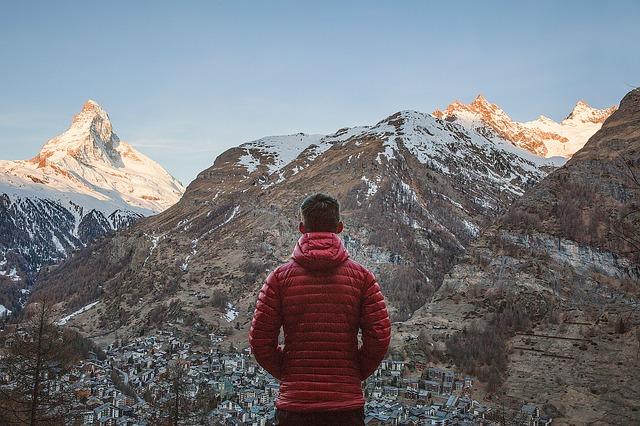 Muž v červenej bunde pozerá na zasnežené hory.jpg