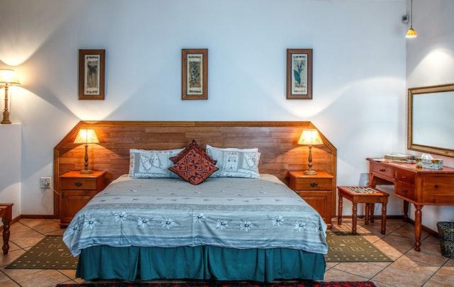 Posteľ s dreveným čelom v historicky zariadenej spálni